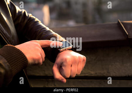 Smartwatch  touchscreen on men's hand and the other hand is working on it. A man using his smartwatch app. Close up hands. - Stock Photo