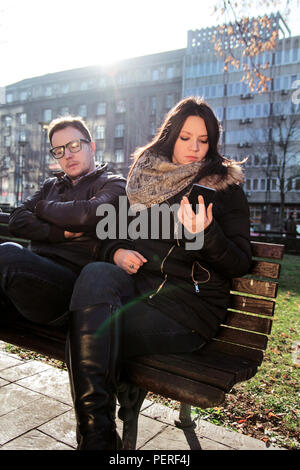 Woman sitting in the park with a man and using smart phone. Couple in love sitting on a park bench, young woman using a smartphone and having fun. - Stock Photo