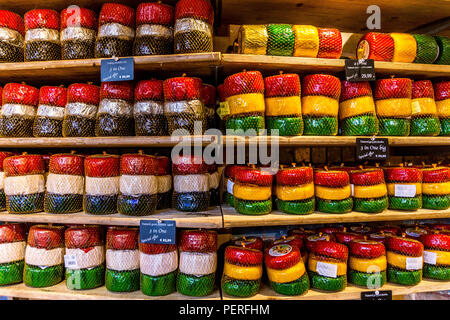 A selection of chesse on display on shelves in a cheese shop, Amsterdam, Netherlands, Europe. - Stock Photo