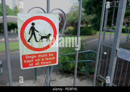 Dogs must be kept on a lead or leash in public park play area sign on entrance gate - Stock Photo
