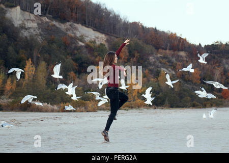 portrait of happy smiling laughing excited Caucasian young woman in jeans running jumping among seagulls birds on autumn fall day outdoor on the shore - Stock Photo