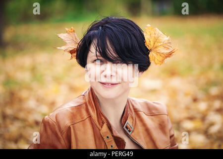 Closeup portrait of middle aged caucasian dark haired brunette woman with short bob hairstyle in light brown leather jacket  looking smiling directly  - Stock Photo