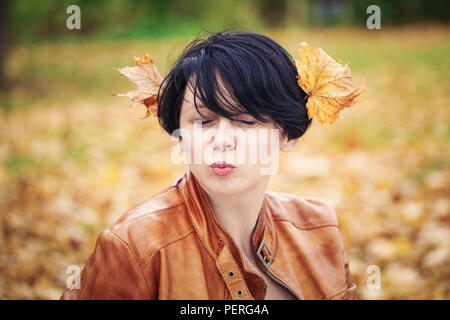 Closeup portrait of middle aged caucasian dark haired brunette woman with short bob hairstyle in light brown leather jacket,  her eyes closed, outside - Stock Photo