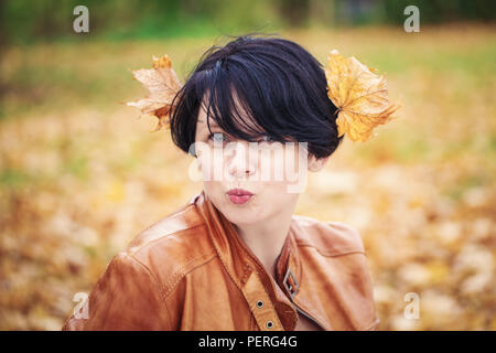 Closeup portrait of middle aged caucasian dark haired brunette woman with short bob hairstyle in light brown leather jacket  looking directly in camer - Stock Photo