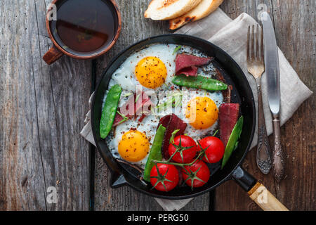 Fried eggs in a frying pan with cherry tomatoes, green peas and pastrami. Copyspace - Stock Photo