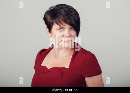 Closeup portrait of beautiful smiling middle aged white caucasian brunette woman with blue eyes in red dress, looking in camera, on light background i - Stock Photo