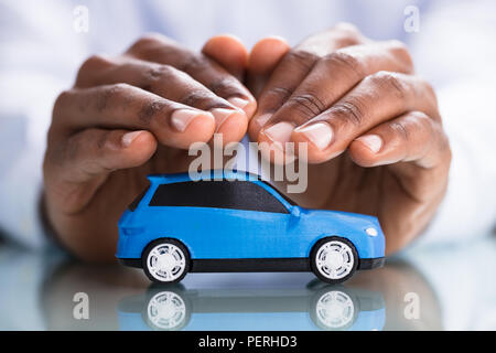 Businessman's Hand Protecting Blue Toy Car On The Reflective Desk - Stock Photo
