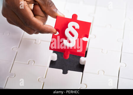 Close-up Of Hand Holding White Paragraph Symbol On Red Jigsaw Puzzle - Stock Photo