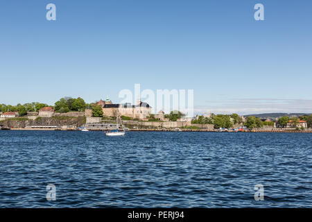 A distant view of Oslo cityscape from the sea with the Akershus fortress in Norway capital city on a sunny day - Stock Photo