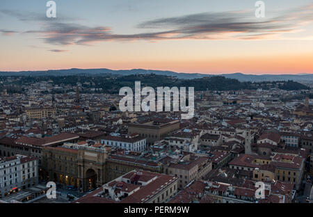 Florence, Italy - March 23, 2018: Evening illuminates the rooftops of Florence city, with the villa-topped hills of Bellosguardo rising behind. - Stock Photo