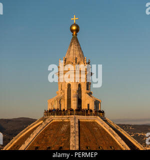 Florence, Italy - March 23, 2018: Tourists gather on the cupola of Florence Cathedral at sunset. - Stock Photo