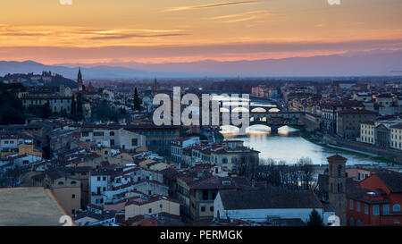 Florence, Italy - March 23, 2018: Evening light illuminates the cityscape of Florence along the Arno River, including the landmark Ponte Vecchio bridg - Stock Photo