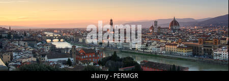 Florence, Italy - March 22, 2018: Afternoon sun illuminates the cityscape of Florence, including the landmark Duomo Cathedral and Ponte Vecchio bridge - Stock Photo