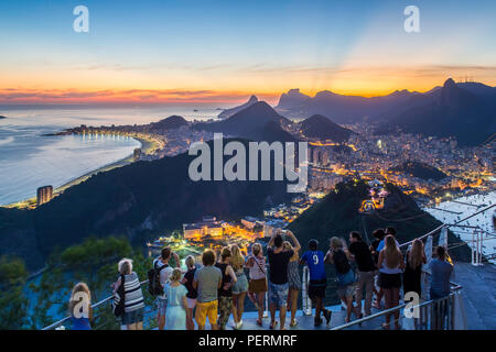 Tourists viewing Christ the Redeemer on Mount Corcovado and the city at sunset from Sugarloaf (Pao de Acucar) in Rio de Janeiro, Brazil - Stock Photo