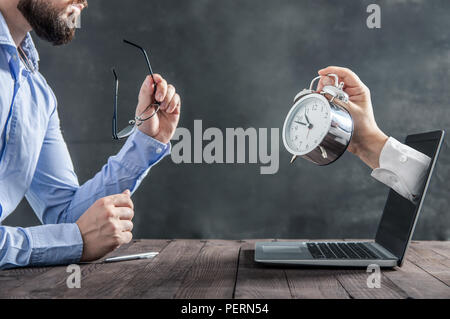 Businessman is sitting at the desk and is looking at the hand with clock coming out of the laptop. Metaphor of spending time at work - Stock Photo