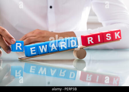 Businessman's hand showing unbalance between reward and risk on wooden seesaw - Stock Photo