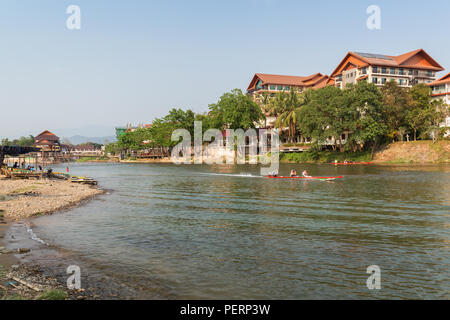 Few people and boats on the Nam Song River and hotels in Vang Vieng, Vientiane Province, Laos, on a sunny day. - Stock Photo