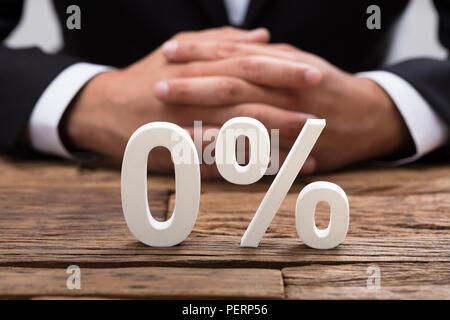 White zero percentage symbol in front of businessperson's hand - Stock Photo