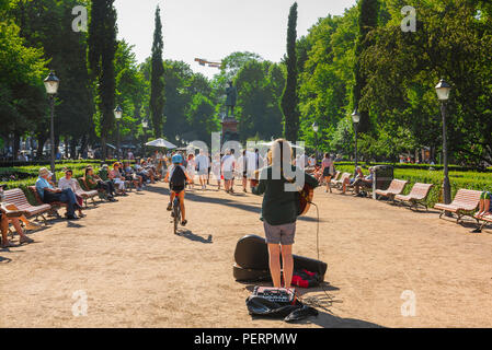Helsinki summer city, rear view of a busker playing his guitar in the Esplanade Park on a summer afternoon in the centre of Helsinki, Finland. - Stock Photo
