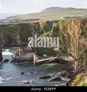 A narrow winding path leads down steep cliffs to Dunquin Pier on the rocky Atlantic Coast of the Dingle Peninsula in Ireland's County Kerry. - Stock Photo