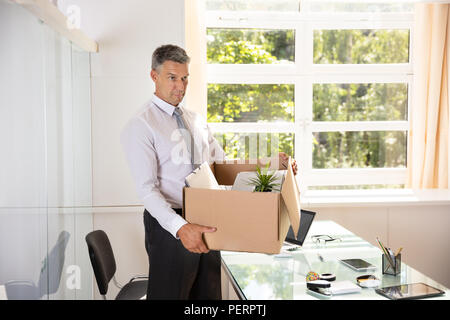 Unhappy Mature Businessman Carrying Belongings In Cardboard Box At Workplace - Stock Photo