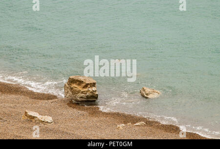 Rocks from a cliff fall on the beach at West bay in Dorset, England, United Kingdom. - Stock Photo