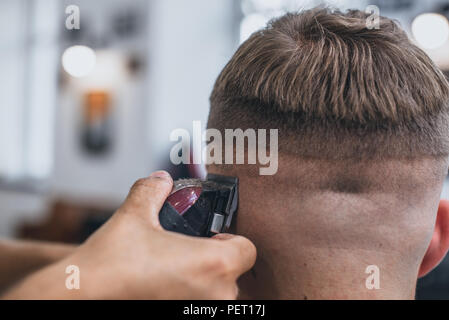 Haircut men Barbershop. Men's Hairdressers barbers. Barber cuts the client machine for haircuts. - Stock Photo