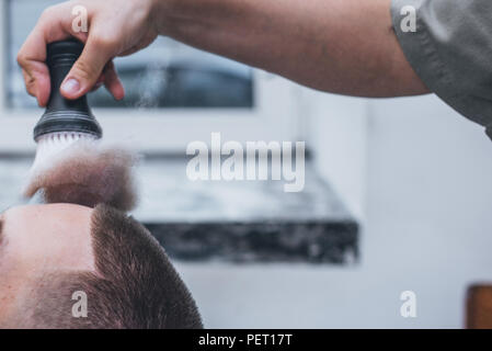 Bearded male sitting in an armchair in a barber shop while hairdresser shaves his beard with a dangerous razor. - Stock Photo