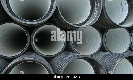 Warehouse of finished plastic pipes industrial outdoors storage site. Manufacture of plastic water pipes factory. - Stock Photo