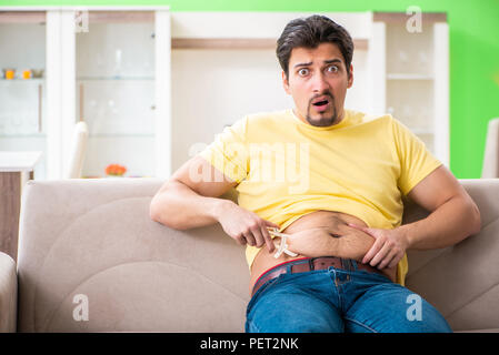 Young man measuring body fat with calipers - Stock Photo