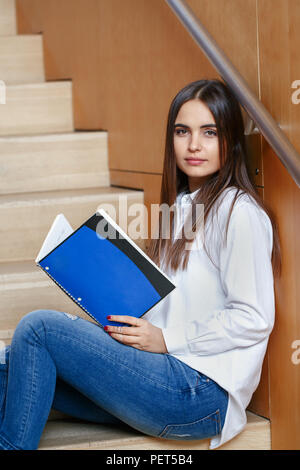 Portrait of pensive Caucasian young girl woman student with dark hair and brown eyes in white shirt and blue jeans, holding notebook sitting on stairc - Stock Photo