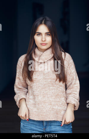 Portrait of pensive serious sad white Caucasian brunette young beautiful woman with long dark hair and brown eyes in turtleneck sweater and blue jeans - Stock Photo