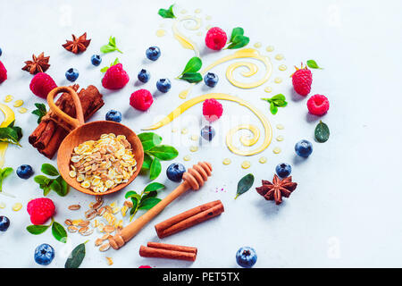 Healthy breakfast concept with oatmeal, honey, cinnamon, and berries on a white wooden background. Cooking porridge flat lay with copy space - Stock Photo
