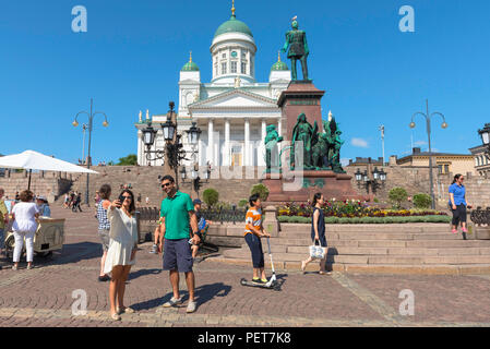 Finland tourism summer, view of a tourist couple in Helsinki posing for a selfie photo in front of the Lutheran Cathedral and Alexander Monument. - Stock Photo