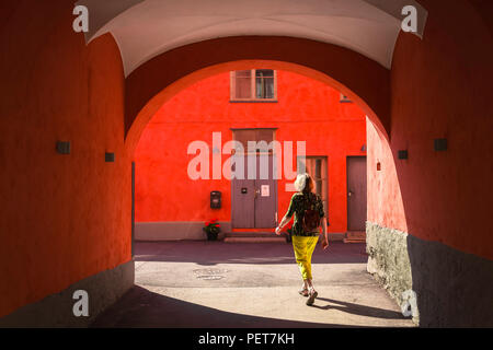 Woman solo travel, rear view of a middle aged female traveller walking alone through a colorful arcade in the old town quarter of Helsinski, Finland. - Stock Photo
