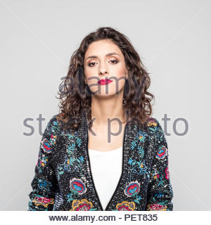 Portrait of beautiful young woman wearing colorful bomber jacket, looking at camera. Studio shot against grey background. - Stock Photo