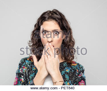 Portrait of surprised young woman, staring at camera and covering mouth by hands, standing against grey background. - Stock Photo