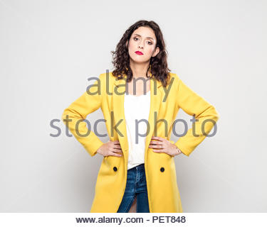 Studio portrait of displeased young woman wearing yellow jacket, standing with arms crossed against grey background. - Stock Photo