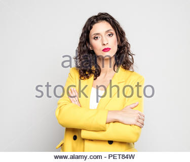 Studio portrait of confident young woman wearing yellow jacket, standing with arms crossed against grey background. - Stock Photo