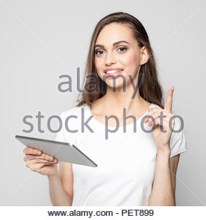 Portrait of beautiful long hair female student wearing white t-shirt, holding a digital tablet and pointing with index finger. Studio shot against gre - Stock Photo