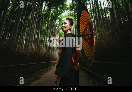 Beautiful japanese senior woman walking in the bamboo forest - Stock Photo
