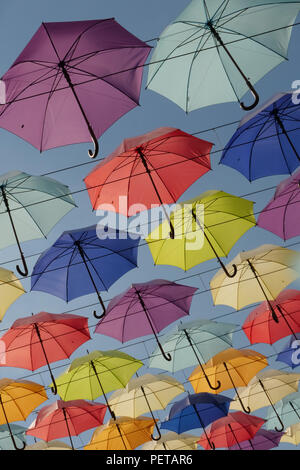 Bright colourful umbrellas hanging on the cords Blue sky background - Stock Photo