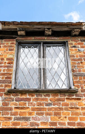 Old leaded window set into red brick wall - Stock Photo