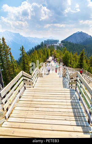 BANFF, CANADA - AUG 1, 2018: Visitors walk the wooden boardwalk on top of Sulphur Mountain between the Gondola summit and Sanson's Peak for a panorami - Stock Photo