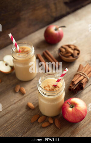 Apple pie protein smoothie drink with almond milk. Homemade apple smoothie with apple pie spices (cinnamon) on wooden background, copy space. - Stock Photo