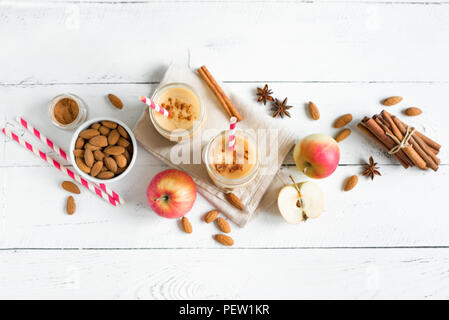 Apple pie protein smoothie drink with almond milk. Homemade apple smoothie with apple pie spices (cinnamon) on white wooden background, copy space. - Stock Photo