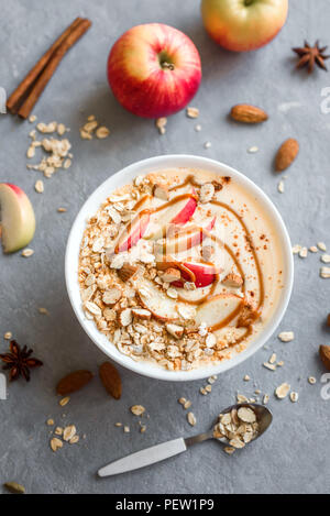 Apple Pie Smoothie Bowl. Breakfast smoothie bowl with apples, cinnamon, almond milk, oat granola and spices, top view. - Stock Photo