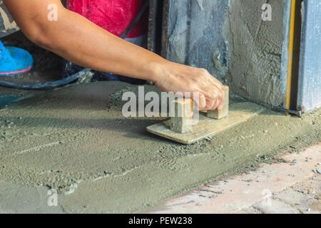 Mason worker use trowel to smooth or leveling liquid concrete of flooring work in step of the building improvement. - Stock Photo
