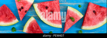 Slices of a ripe watermelon with mint leaves on a blue wooden background. Banner. - Stock Photo