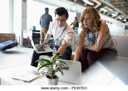 Businessman and businesswoman talking, using laptops in office lounge - Stock Photo